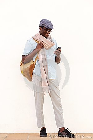 Full length trendy young black guy looking at cell phone and smiling