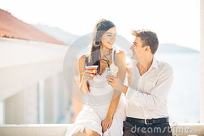 Attractive couple drinking cocktails ,enjoying summer vacation.Smiling,attracted to each other.Flirting and seduction