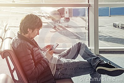 Young man in jeans and jacket sits on chair spend time by using mobile phone in airport lounge. Booking hotel in foreign country.