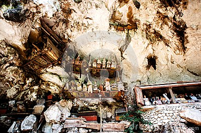 The cemetery with coffins placed in cave and balconies with wooden statues tau tau. Old burial site in Londa, Tanaja, Indonesia