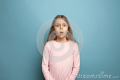 stock image of the surprise. teen girl on a blue background. facial expressions and people emotions concept
