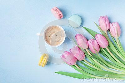 Spring tulip flowers, colorful macaroons and coffee on blue pastel table top view. Beautiful breakfast on Mothers or Womans day.