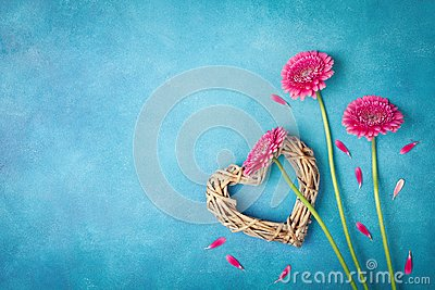 Spring background with pink flowers, heart and petals. Greeting card for Woman day. Flat lay style. Top view.