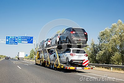Car carrier trailer with new cars for sale on bunk platform. Car transport truck on the highway