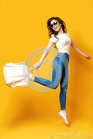 Beautiful young woman in sunglasses, white shirt, blue jeans jumping with bag on the yellow background