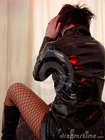 woman in black pvc coat and red fishnet stockings