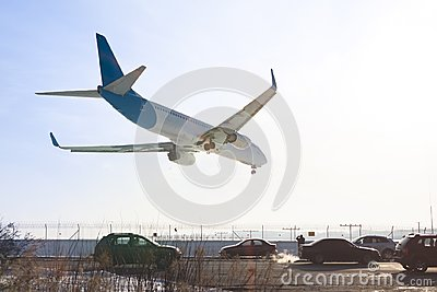 Tail view of landing airplane. Aircraft flying over highway. Road with high traffic near airport runway. Type of transport compar