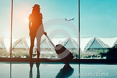 stock image of silhouette woman travel with luggage looking without window at airport terminal international or girl teenager traveling in vacati