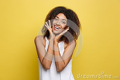 Smiling beautiful young African American woman in white T-shirt posing with hands on chin. Studio shot on Yellow
