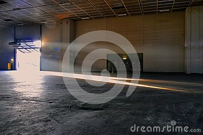 Panoramic view of empty industrial plant site beam of sunlight enters the raised gate