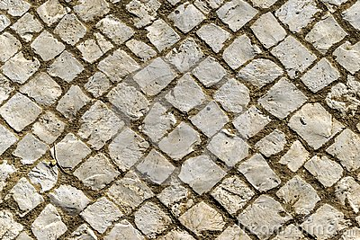 Background of old irregular inclined cobblestones