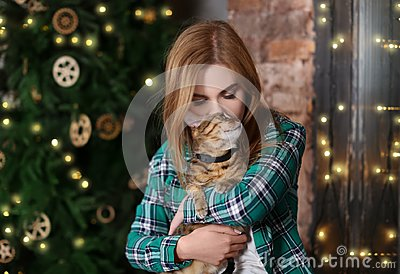Beautiful young woman with cute cat near   tree at home