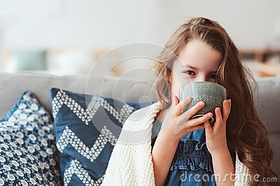 child girl drinking hot tea to recover from flu