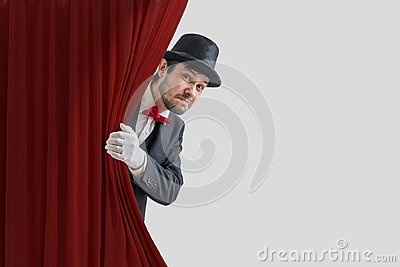 Nervous actor or illusionist is hiding behind red curtain in theater