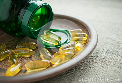 Yellow vitamin D3 cholecalciferol gelatine capsules and green