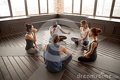 African-american yoga instructor talking to diverse group sittin