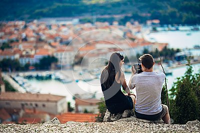 Cheerful young couple having a field trip date.Cityscape sightseeing,seaside travel vacation.Traveling in Europe