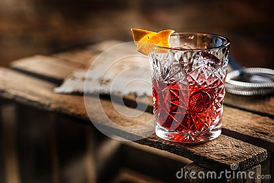 Cocktail Negroni on a old wooden board. Drink with gin, campari