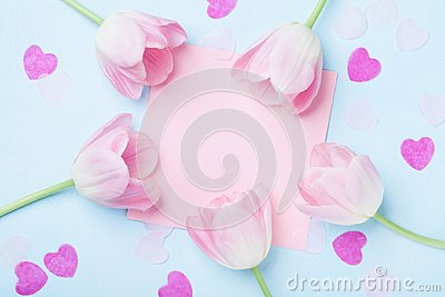 Birthday or wedding mockup with pink paper list, hearts and tulip flowers on blue background top view. Beautiful woman day card.