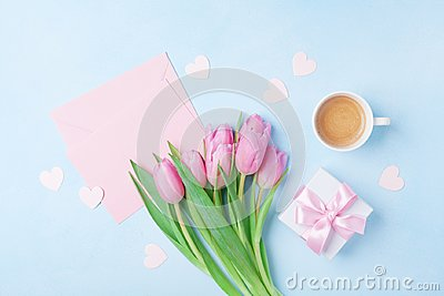 Coffee cup, spring tulip flowers, gift box and pink paper card on blue pastel table top view. Greeting for Womans or Mothers Day.