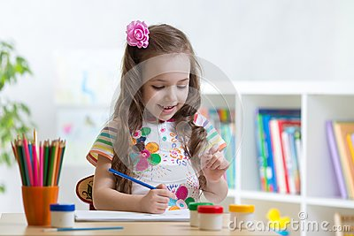 Cute little preschooler child girl drawing color pencils at home or studio