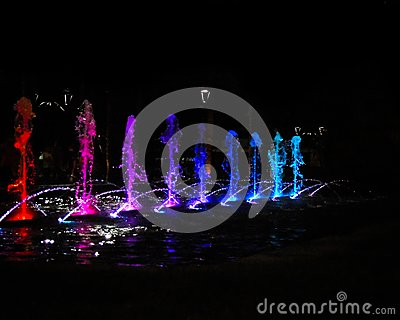 Red, purple, blue and aqua water gushes splashing at night.