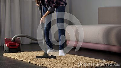 Female hoovering room carpet during general cleaning, house working, tidiness