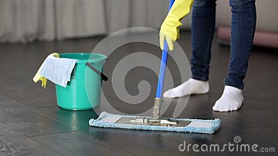 Obsessive with cleanliness young lady thoroughly washing floor of her house