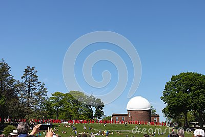 Someone takes a phone photo of graduates filing in front of observatory at Wesleyan University Graduation Middletown Conneticut US