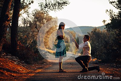 Man in love proposing a surprised,shocked woman to marry him.Proposal, engagement and wedding concept.Betrothal.Being affianced