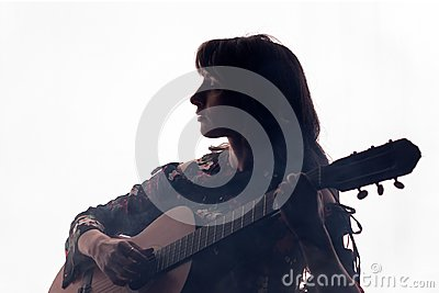 Silhouette. Beautiful girl plays on an acoustic guitar on a white background in a haze. Copy space. A square picture.