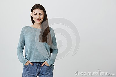 Attractive adult women with long hair, wearing blue sweater and jeans, smiling and stand with hands in pockets over gray