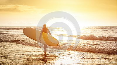 Guy surfer walking with surfboard at sunset in Tenerife - Surf concept