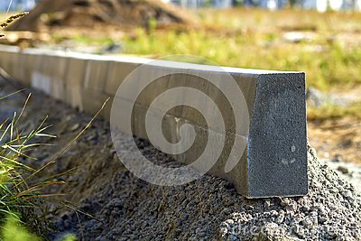 Concrete curb installation works at road construction site. Shallow DOF.