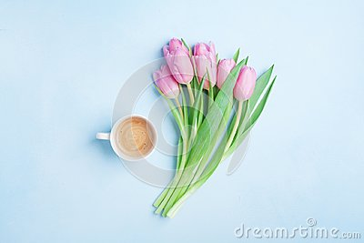 Fresh coffee and pink tulip flowers on pastel background top view. Beautiful spring breakfast on Mothers or Womans day. Flat lay.