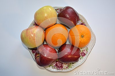 stock image of a dish of fruit. ripe apples and oranges