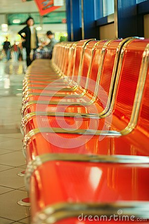 Empty red metal seats at airport hall