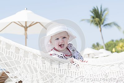 Beautiful Happy Expressive Blond Girl Toddler with Sun Protection in a Pool