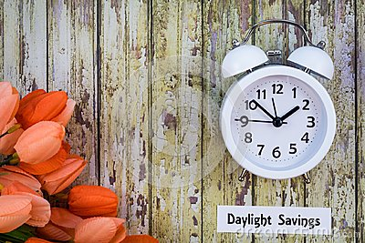 Daylight Savings Time Spring concept top down view with white clock and orange tulips