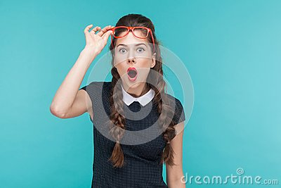 Surprised woman in red glasses amazement looking at camera