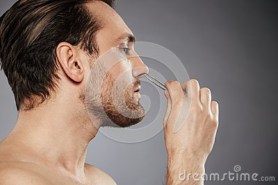 Side view portrait of a confident man removing nose hair