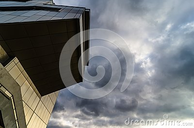 View through modern high rising skyscraper upwards to blue sky with white clouds - abstract architecture detail background