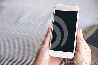 Mockup image of hands holding white mobile phone with blank black desktop screen and laptop