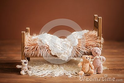 Cot for a newborn on a brown background with toys and a white rug, background