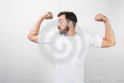 A handsome confident young man standing and showing big muscles on his hands. He is looking at one of them and very