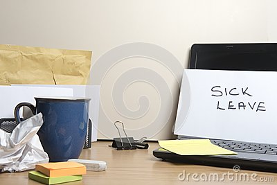 Sick leave message left on a messy office desk