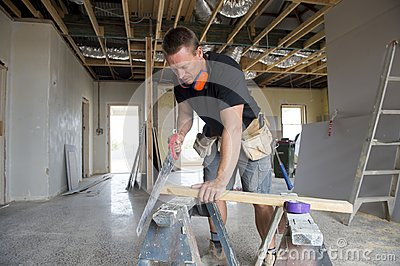 Attractive and confident constructor carpenter or builder man working cutting wood with manual saw in industrial construction job