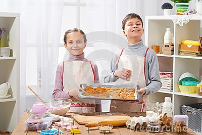 Boy and girl shows a tray of baked cookies in home kitchen interior, homemade food concept