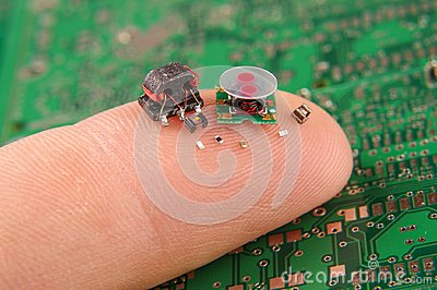 stock image of small electronics components on human finger