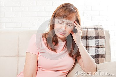 Middle aged woman having headache. Homey concept. Menopause and depression. Copy space